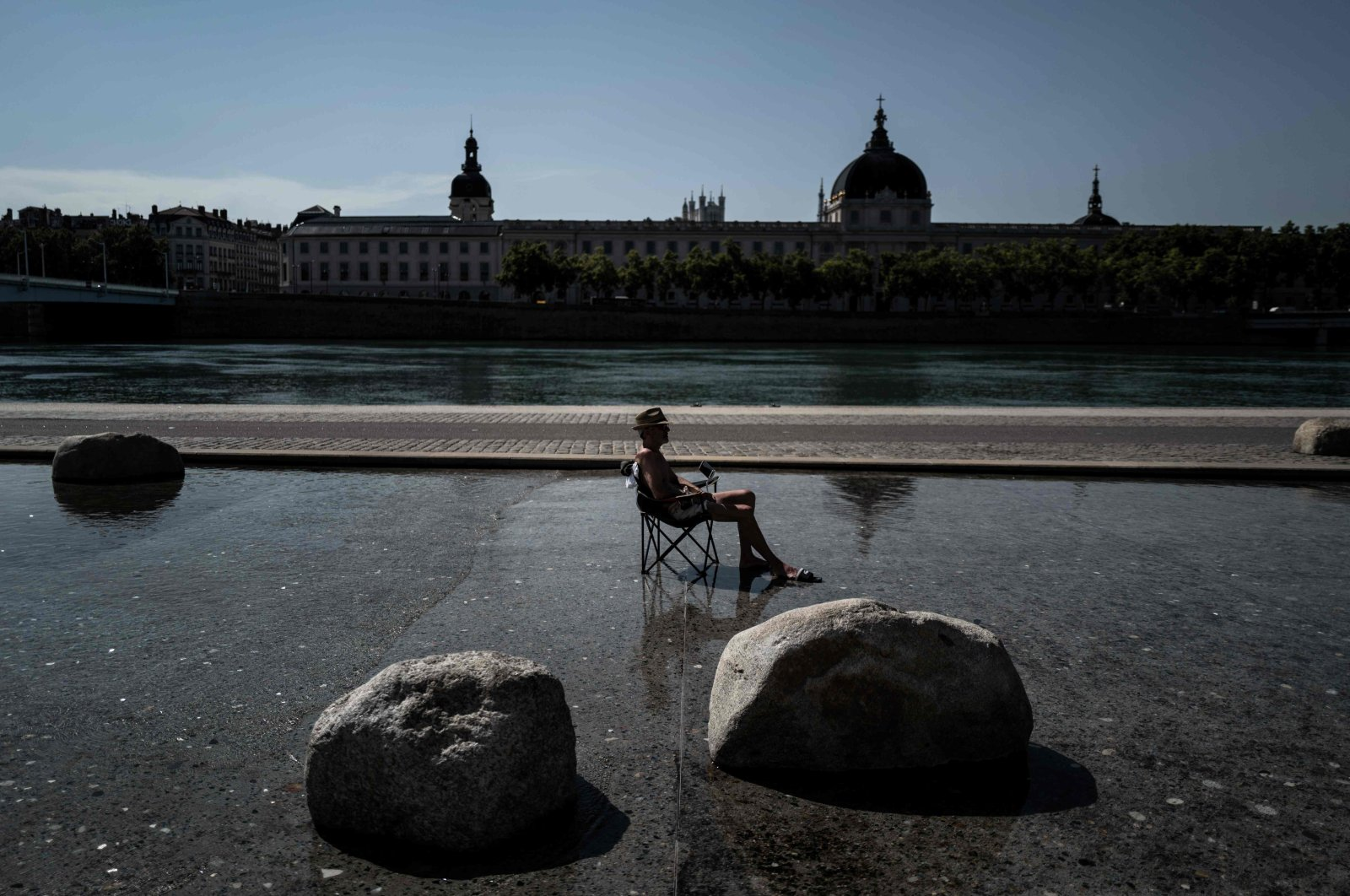 A man cools off in a water basin in the center of Lyon, as a heatwave hits France, July 30, 2020. (AFP Photo)