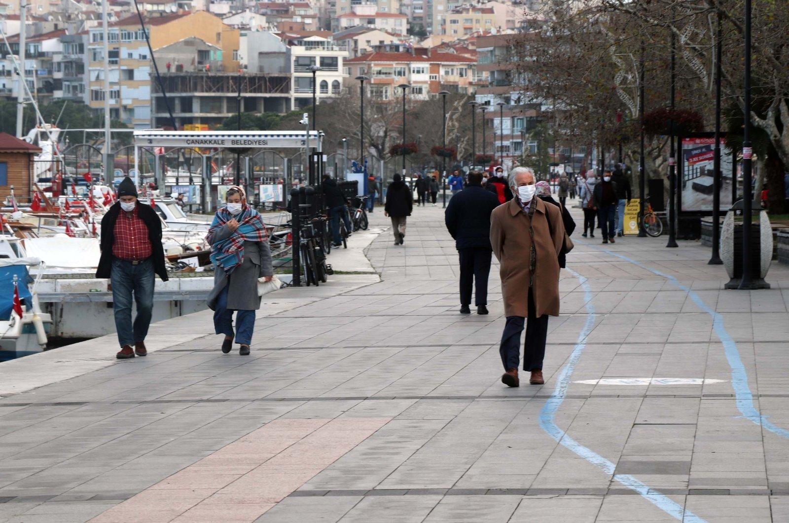 People wearing protective masks walk on the coast, in Çanakkale, western Turkey, Jan. 5, 2021. (DHA Photo)