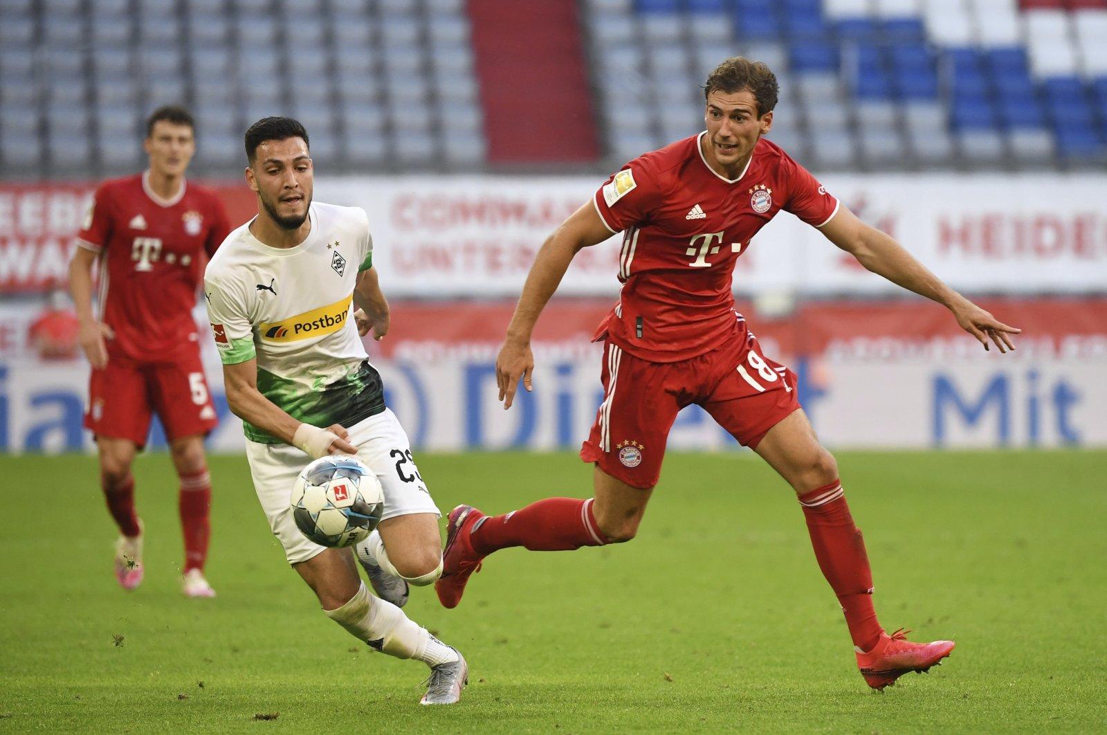 Bayern Munich's Leon Goretzka (R), and Borussia Moenchengladbach's Ramy Bensebaini compete for the ball during a Bundesliga match at the Allianz Arena stadium, in Munich, Germany, June 13, 2020. (AP Photo)