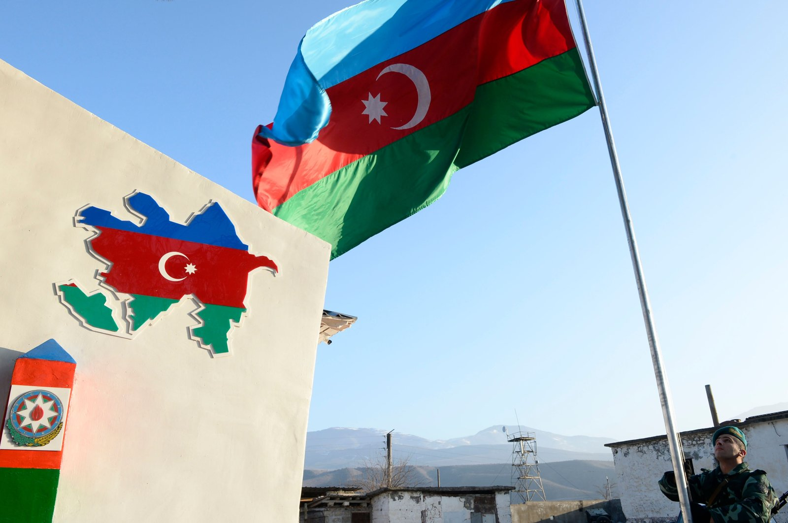 An Azerbaijani border guard raises the national flag during the opening ceremony of the frontier post in the village of Zangilan, Azerbaijan, Jan. 5, 2021. (AFP Photo)
