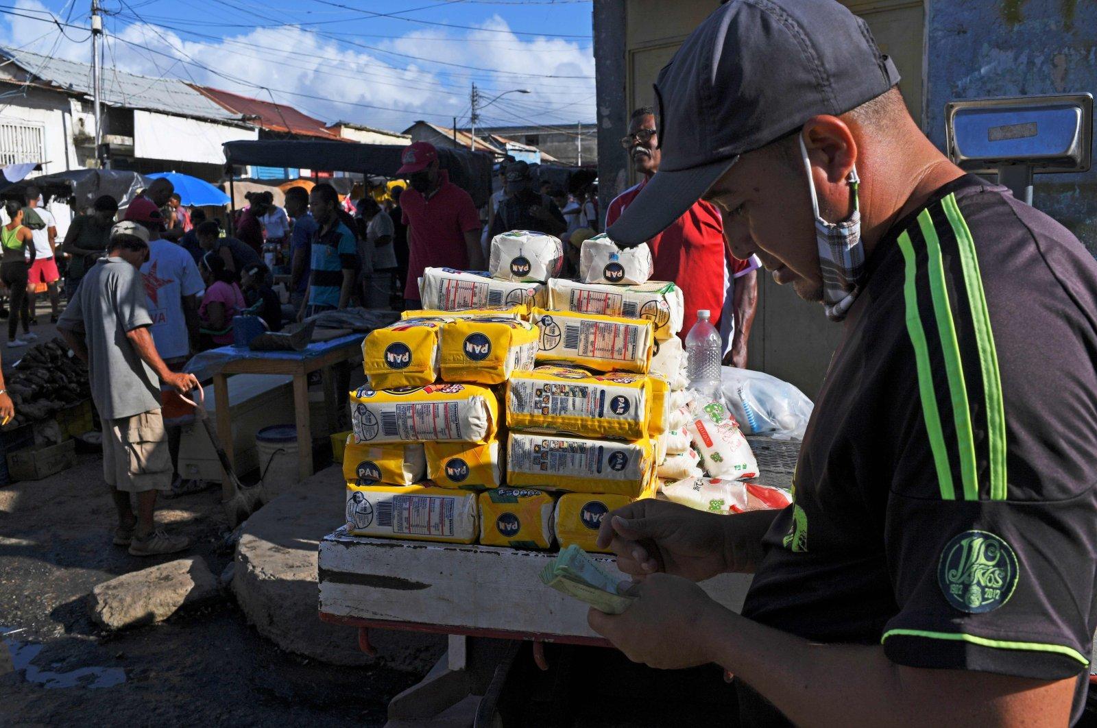 A Venezuelan merchant waits for customers as he sells corn flour at the street market in Guiria, Venezuela, Dec. 19, 2020. (AFP Photo)