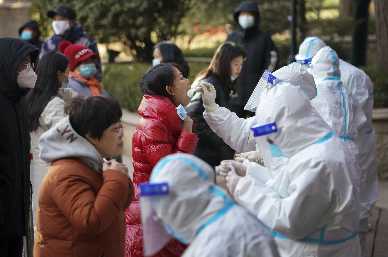 In this photo released by Xinhua News Agency, medical workers in protective suits take swabs from residents near a residential area in Shijiazhuang in north China's Hebei province, Jan. 6, 2021. (AP Photo)