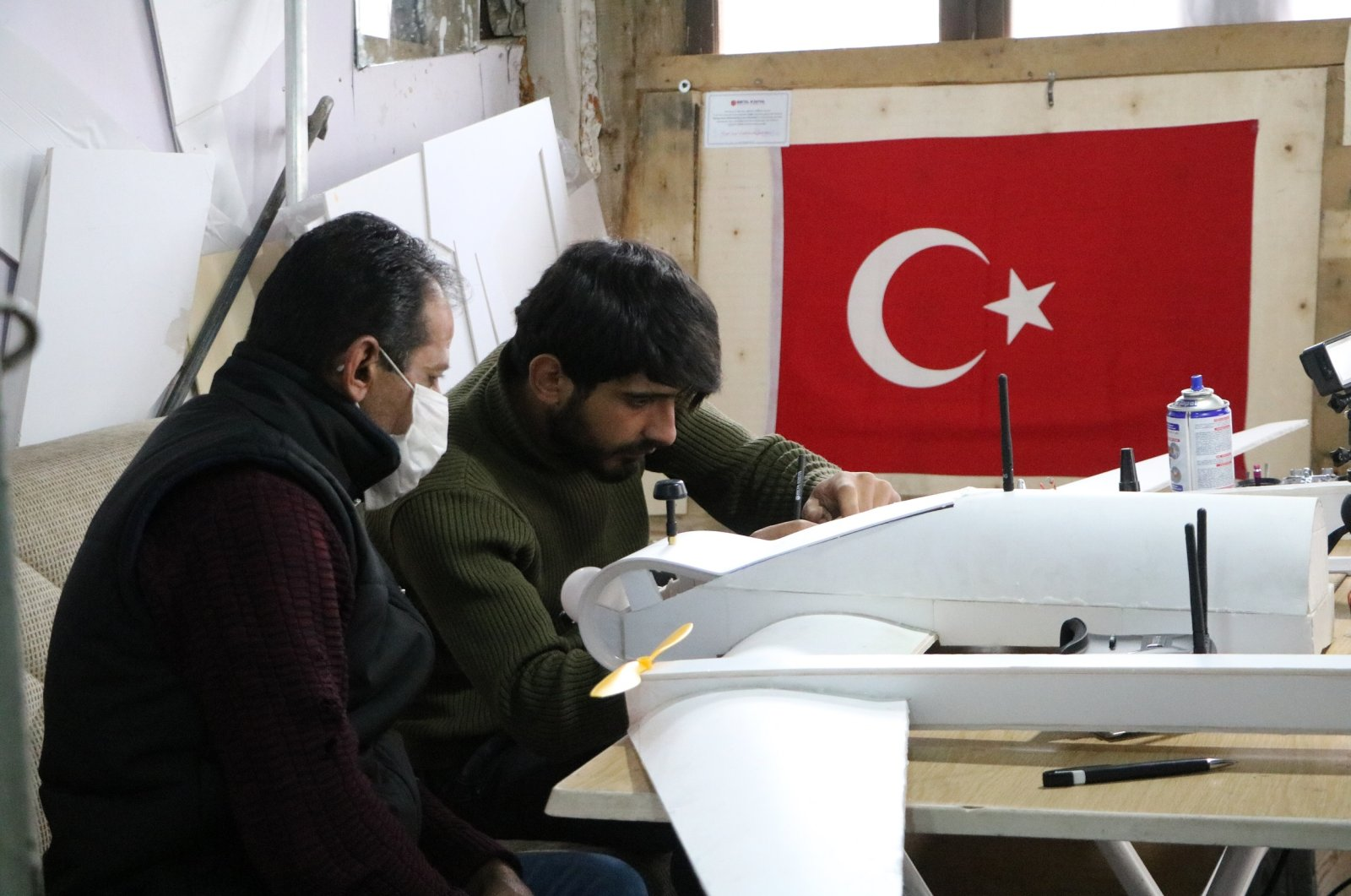 Savaş Tatlı (R), a contestant of TEKNOFEST 2020, and his father work on a model plane in their atelier in eastern Hakkari province on Dec. 17, 2020. (DHA Photo)