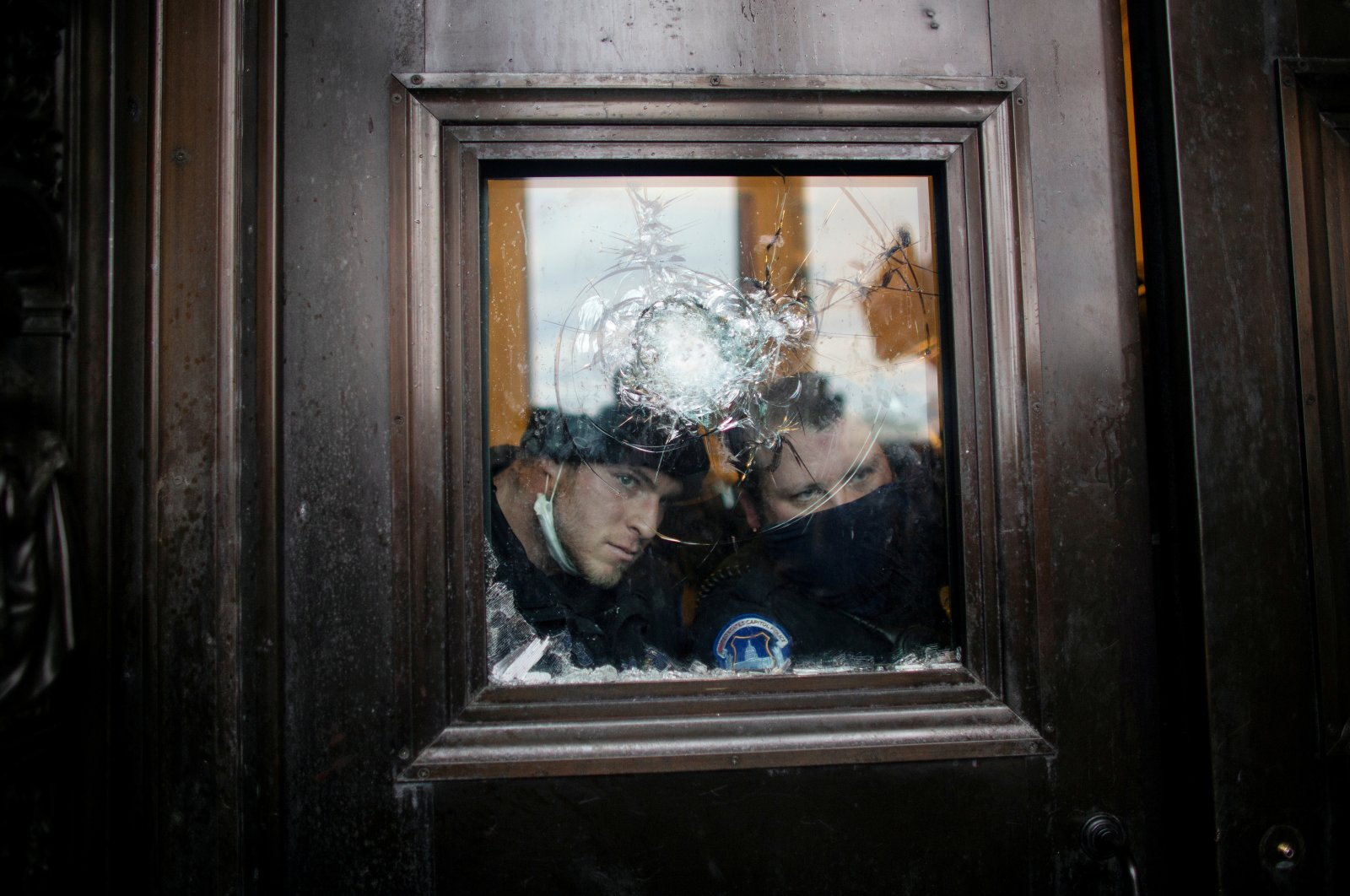 Members of the Capitol police look through a smashed window as pro-Trump protesters rally to contest the certification of the 2020 U.S. presidential election results by the U.S. Congress, at the U.S. Capitol Building in Washington, D.C., U.S. Jan. 6, 2021. (Reuters Photo)