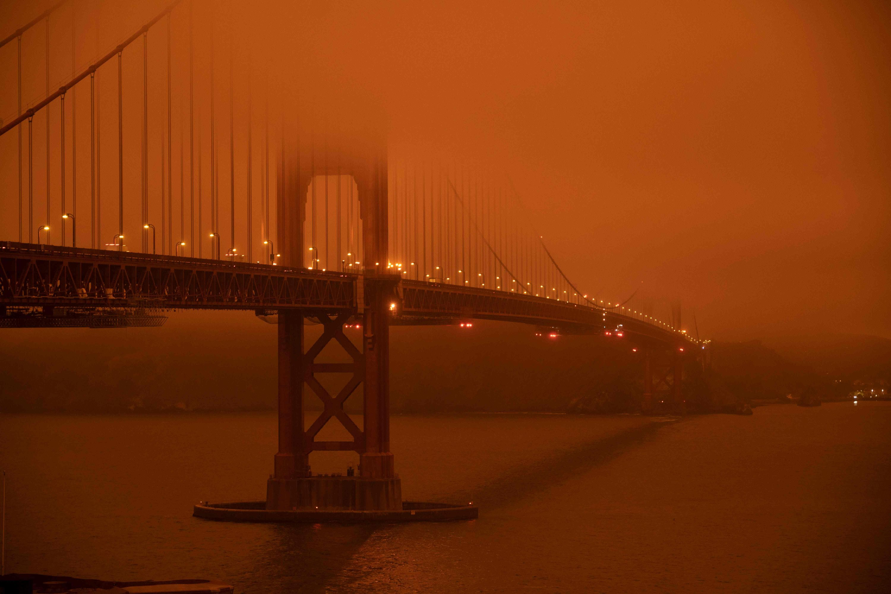 Cars drive along the Golden Gate Bridge under an orange smoke-filled sky at midday in San Francisco, California, U.S., Sept. 9, 2020. (AFP Photo)