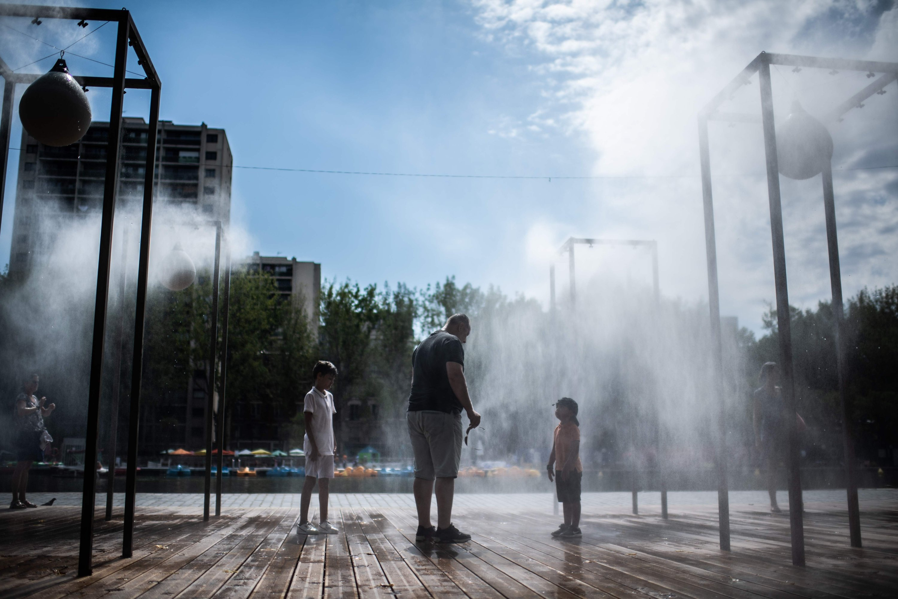 A man and children cool off under a water spray in Paris, as France faces a heat wave, Aug. 8, 2020. (AFP Photo)
