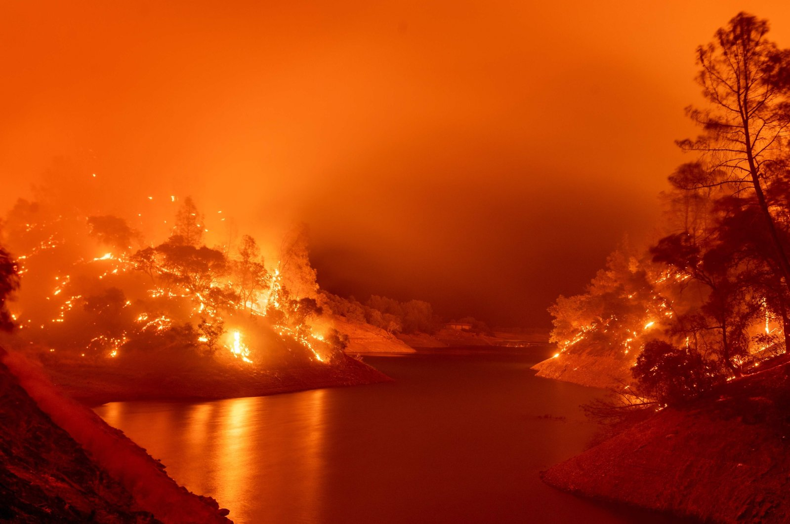 In this long exposure photograph, flames consume both sides of a segment of Lake Berryessa during the Hennessey fire in the Spanish Flat area of Napa, California, U.S., Aug. 18, 2020. (AFP Photo)