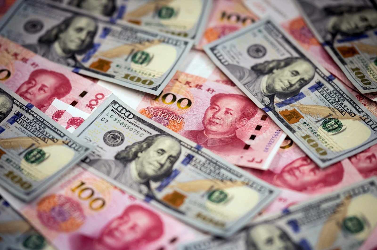 Chinese 100-yuan notes and US 100-dollar notes seen in this photo illustration, Beijing, China, Jan. 14, 2020. (AFP Photo)