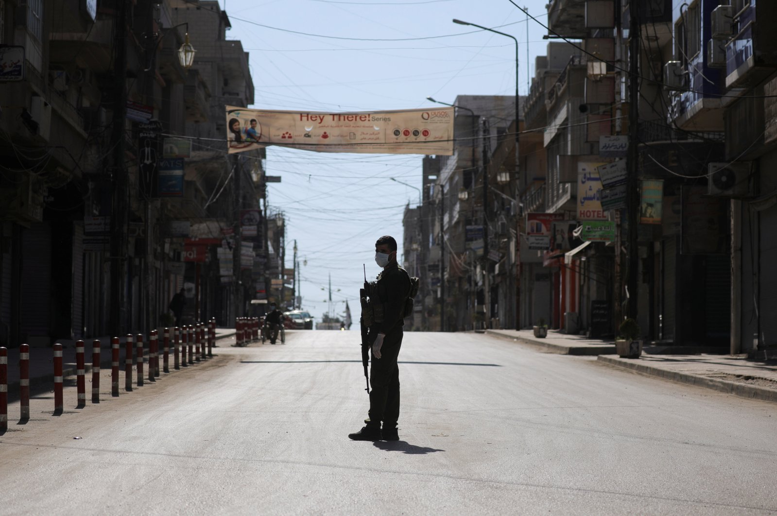 A YPG/PKK member stands near closed shops along an empty street as restrictions are imposed as a measure to prevent the spread of the coronavirus in Qamishli, Syria, March 23, 2020. (Reuters Photo)