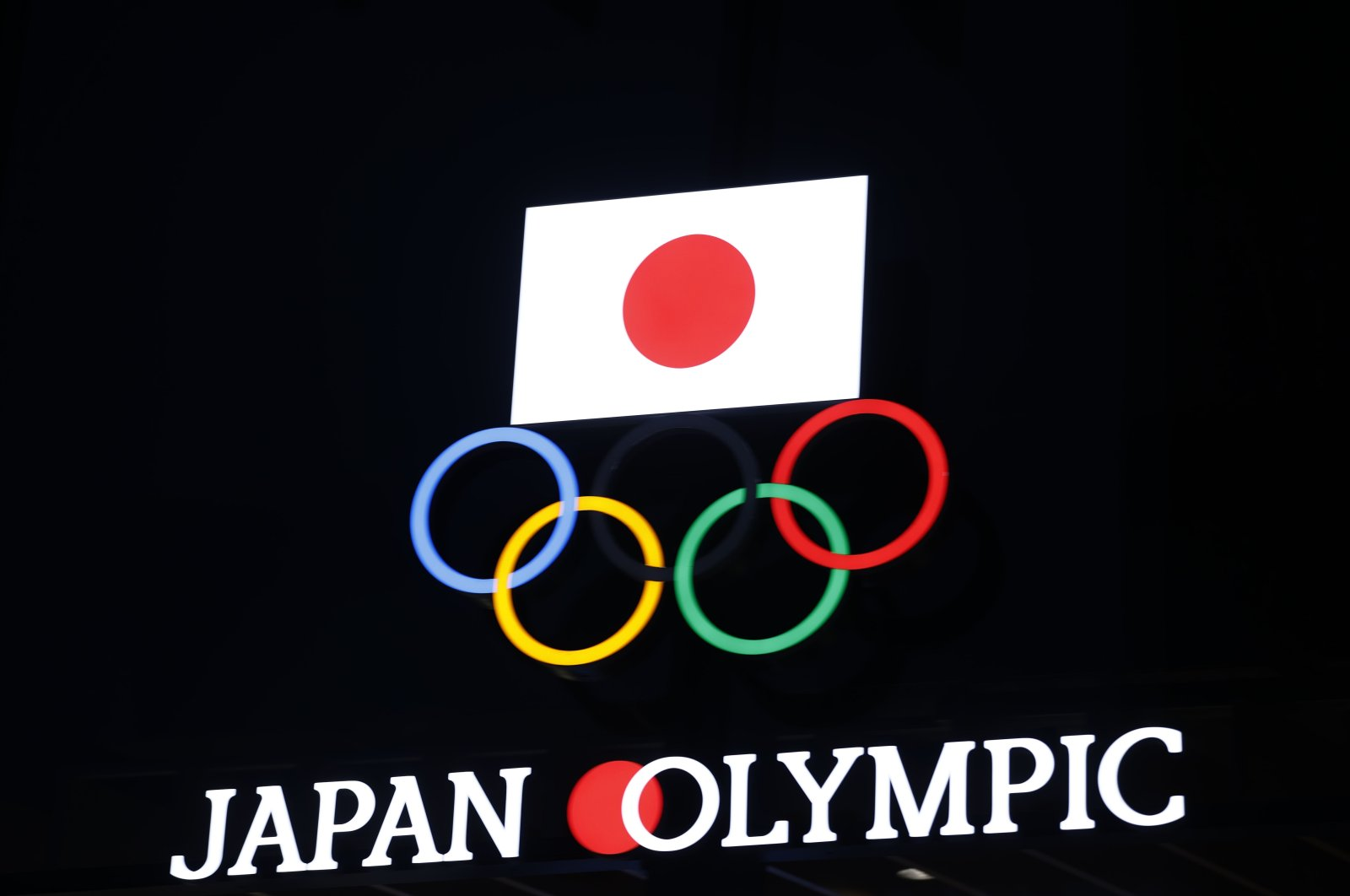The Olympic rings and a Japanese flag on display at the Japan Olympic Museum building in Tokyo, Japan, Jan. 8, 2021. (AFP Photo)