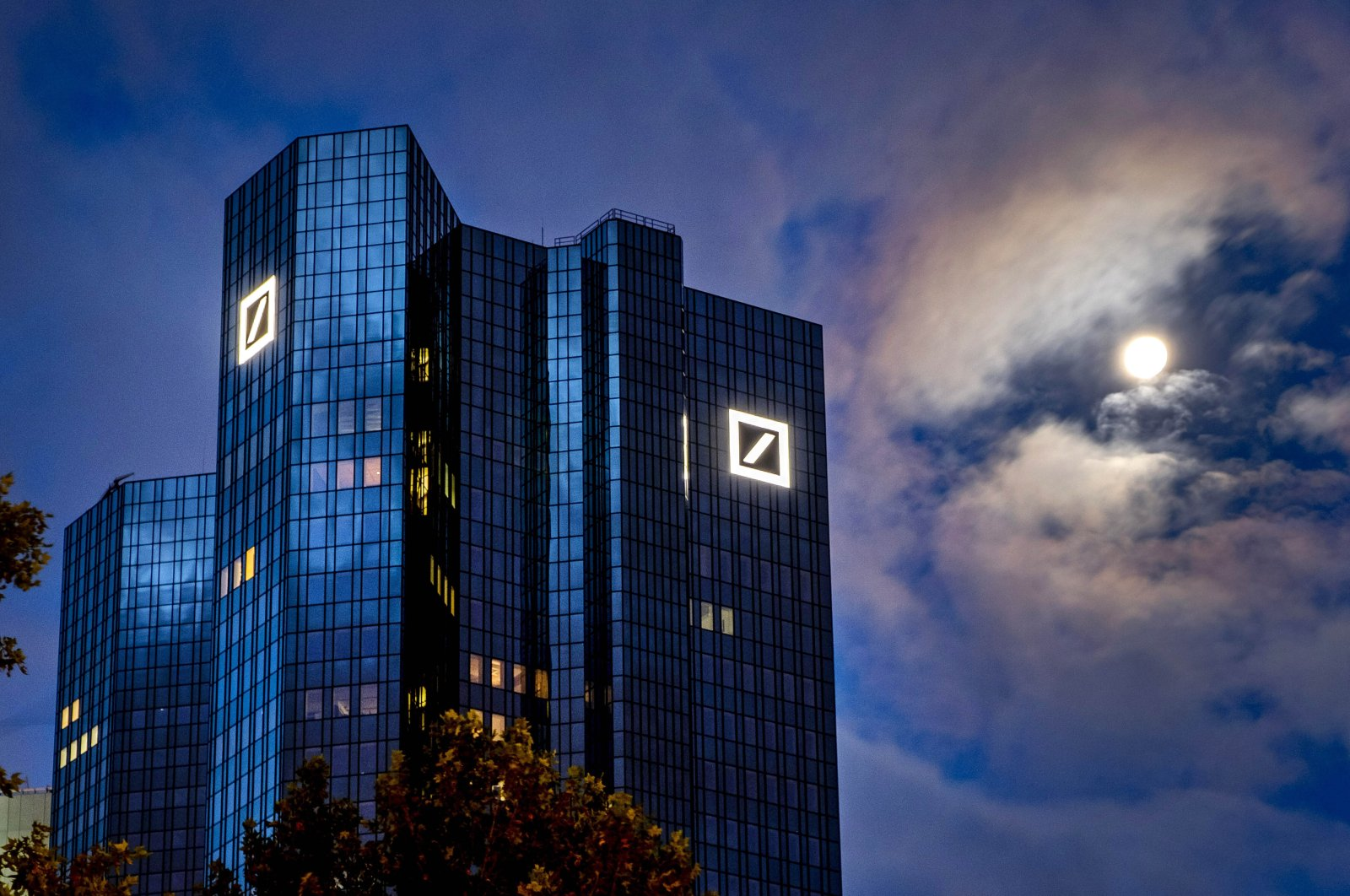 The moon shines next to the headquarters of the Deutsche Bank in Frankfurt, Germany, Oct. 4, 2020. (AP Photo)