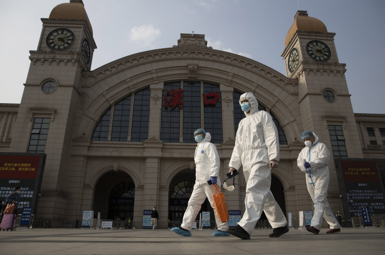 Workers in protective suits walk past the Hankou railway station on the eve of its resuming outbound traffic in Wuhan, Hubei province, central China, April 7, 2020. (AP Photo)