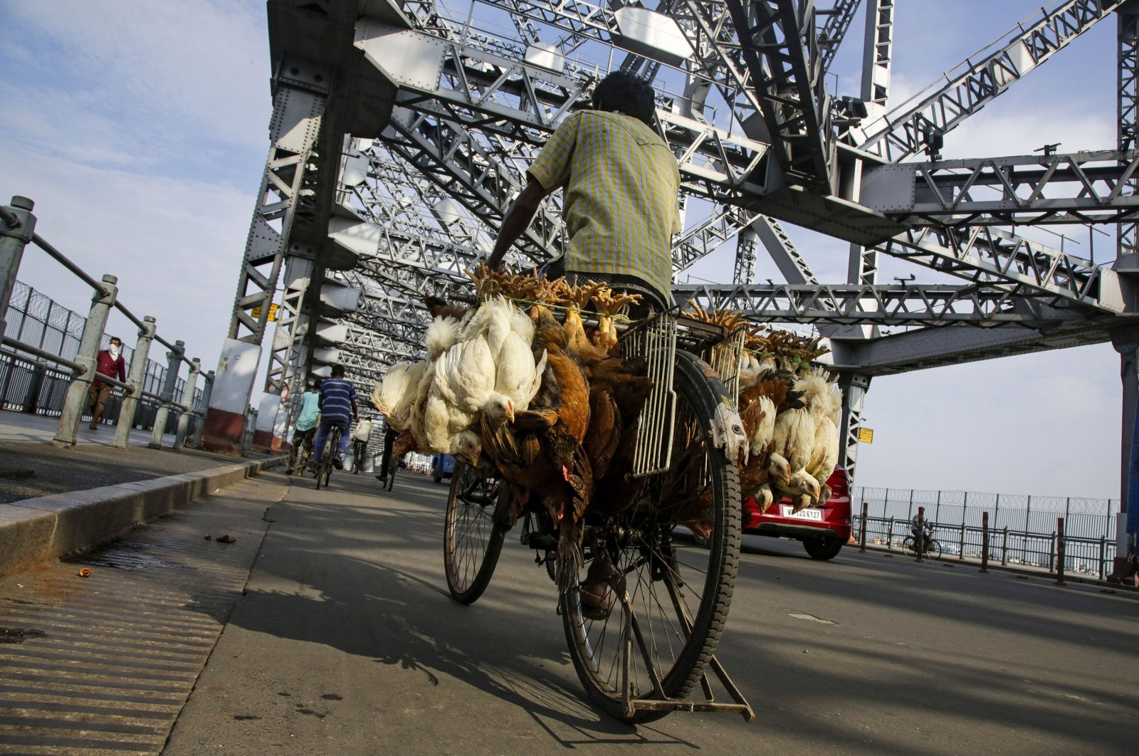 A vendor carries chickens for sale and rides past the landmark Howrah Bridge in Kolkata, in the state of West Bengal, eastern India, June 3, 2020. (AP Photo)