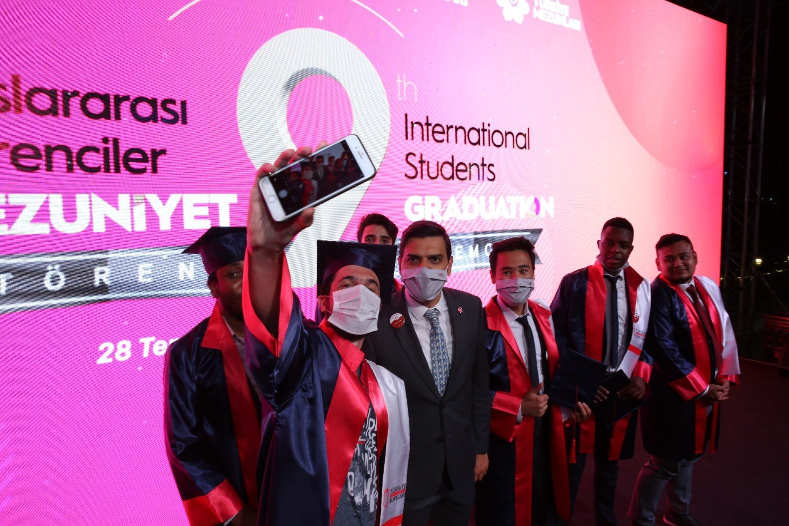 Students pose with YTB President Abdullah Eren (C) during graduation ceremony, in the capital Ankara, Turkey, July 28, 2020. (Photo courtesy of YTB)