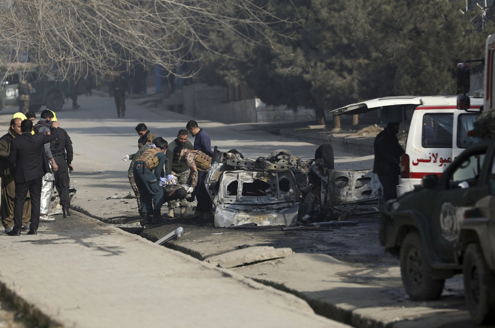 Afghan security officers carry the body of a man from the site of a bomb attack in Kabul, Afghanistan, Jan. 10, 2021. (AP Photo)