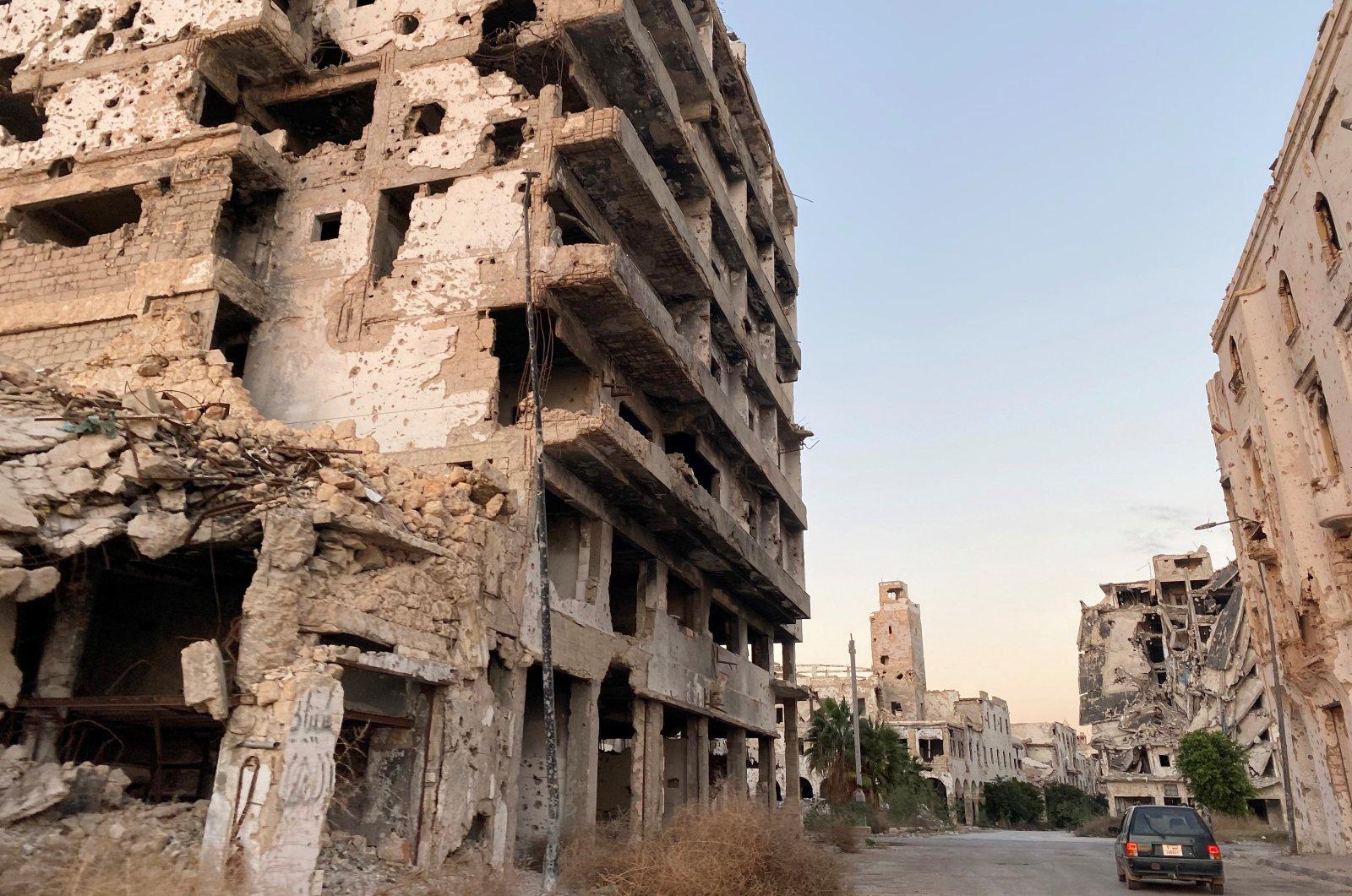 A car sits between destroyed buildings in Benghazi, Libya, Nov. 23, 2020. (Reuters Photo)