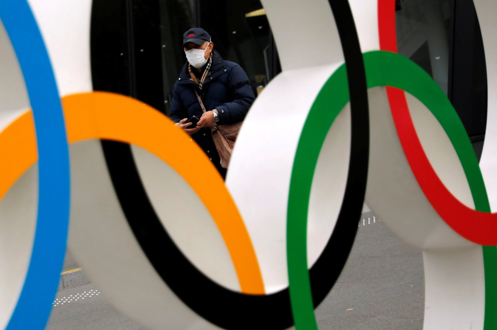 A man wearing a protective mask seen through the Olympic rings, in Tokyo, Japan, Jan. 8, 2021. (Reuters Photo)