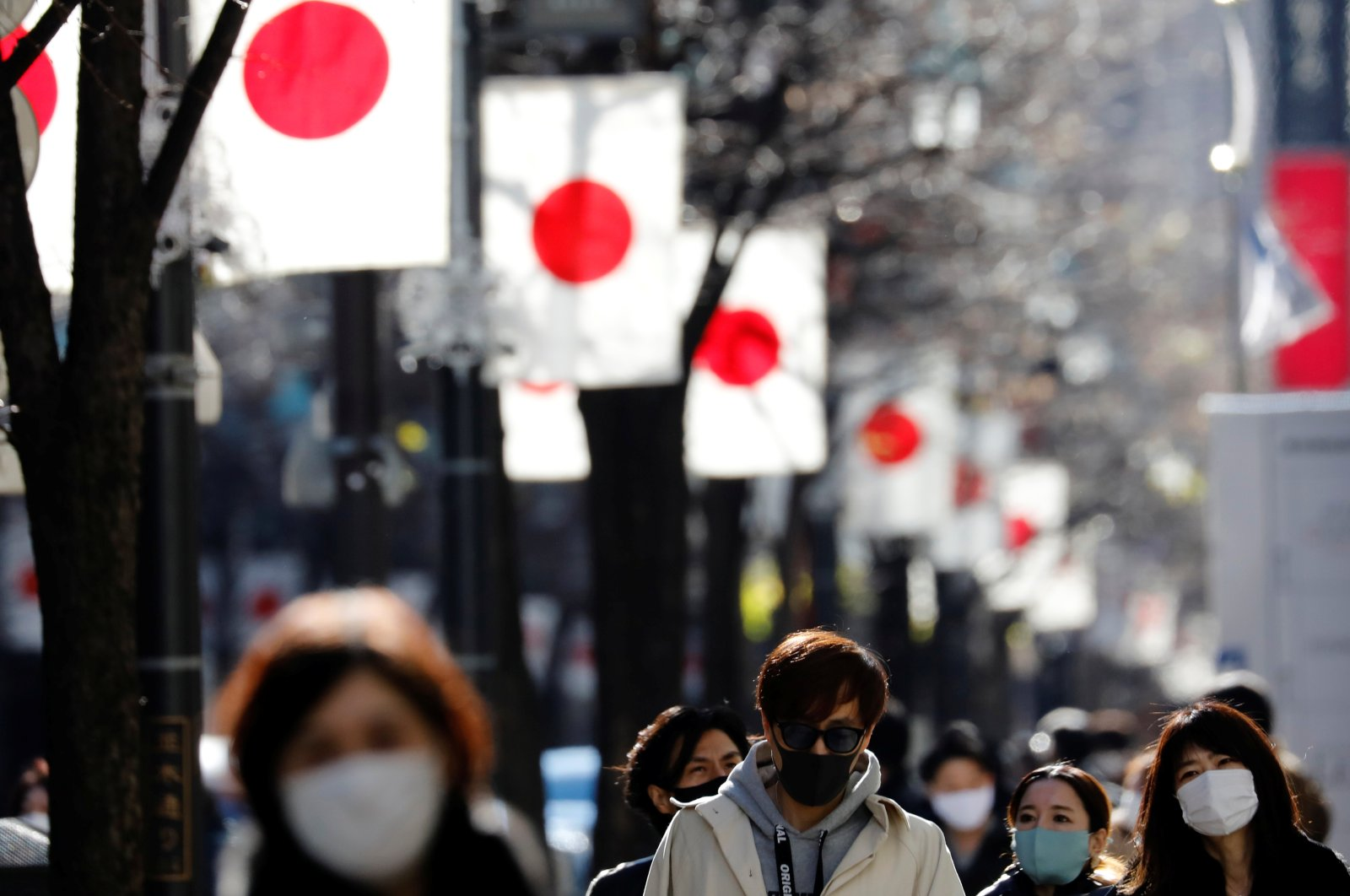 Pedestrians wearing protective masks, amid the coronavirus disease (COVID-19) outbreak, make their way to Ginza shopping district which closed to cars in Tokyo, Japan, Jan. 10, 2021. (Reuters Photo)
