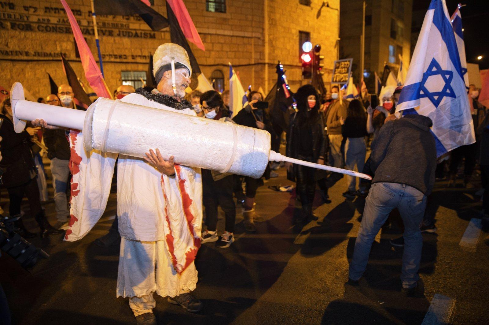 An Israeli protester holds a giant syringe during a demonstration against Israeli Prime Minister Benjamin Netanyahu near his official residence during the third nationwide coronavirus lockdown, Jerusalem, Jan. 9, 2021. (AP Photo)