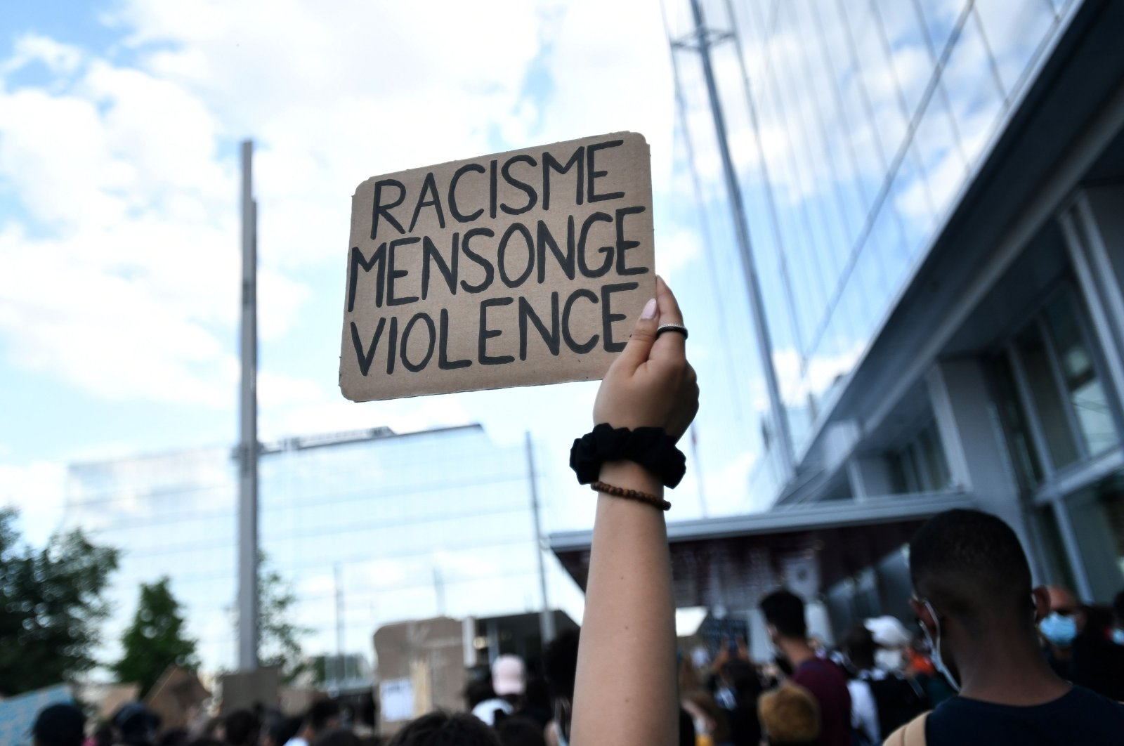 """A protester holds a placard reading """"Racism, lies, violence"""" during a demonstration after French medical experts exonerated the gendarmes involved in the arrest of Adama Traore, a young black man who died in police custody in 2016, outside the """"Tribunal de Paris"""" courthouse in Paris. June 2, 2020. (AFP Photo)"""