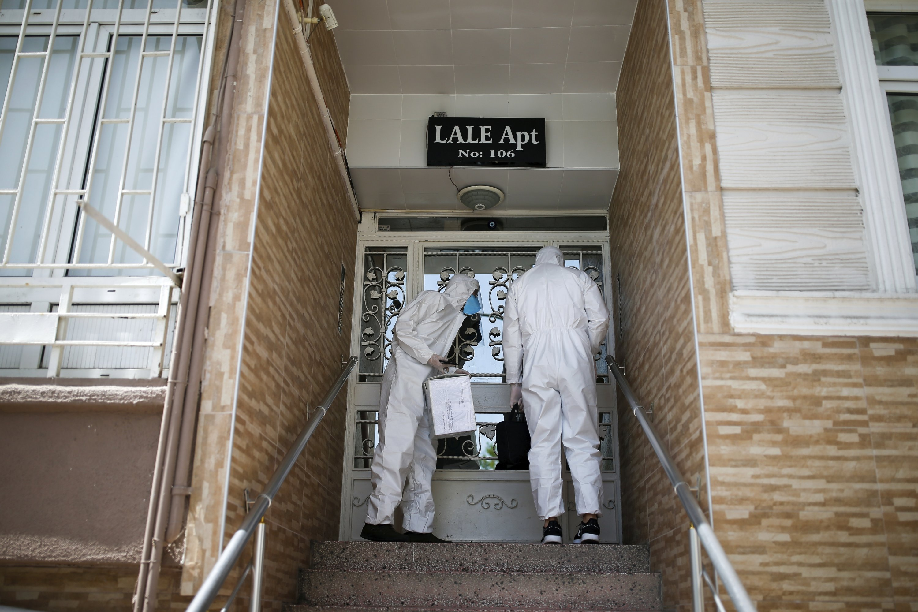 In this Friday, May 15, 2020 photo, contact tracers with Turkey's Health Ministry's coronavirus contact tracing team visit houses to take samples from suspected patients. (AP Photo)