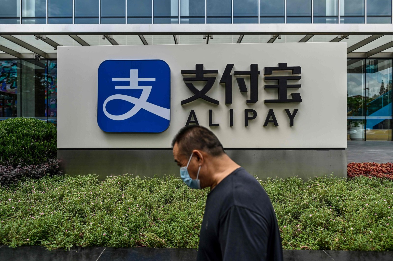 A pedestrian walking past an Alipay logo at the Shanghai office building of Ant Group in Shanghai, China, Aug. 28, 2020. (AFP Photo)