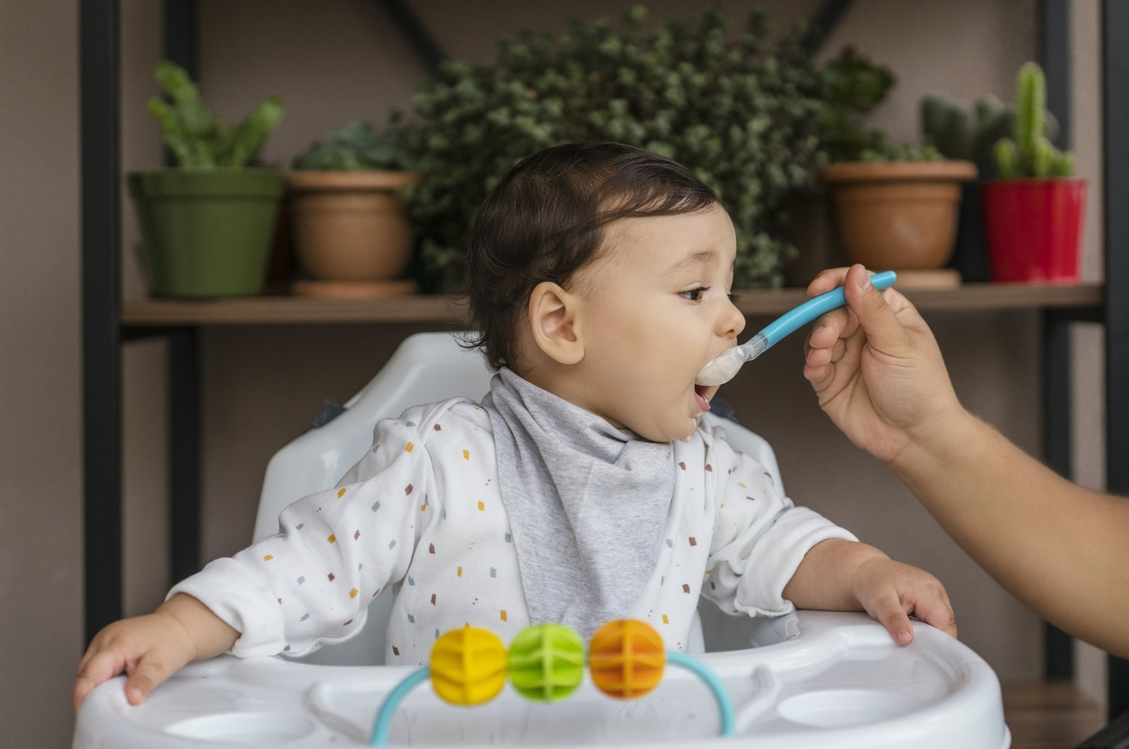 A baby sitting in a high chair is fed off of a spoon. (iStock Photo)