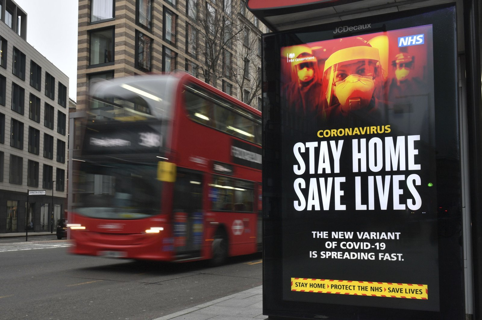 A London Transport famous red bus passing a COVID-19 sign during England's third national lockdown to curb the spread of coronavirus, London, the U.K., Friday, Jan. 8, 2021. (AP Photo)