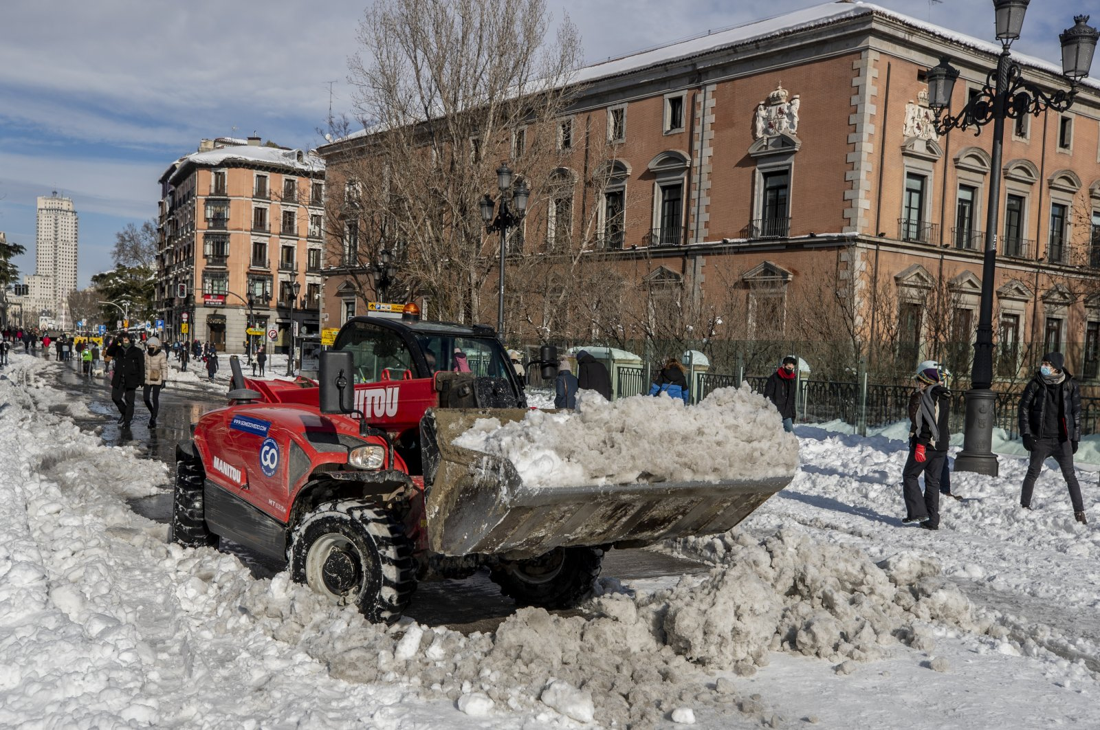 A plough clears snow in downtown Madrid, Spain, Sunday, Jan. 10, 2021. (AP Photo)