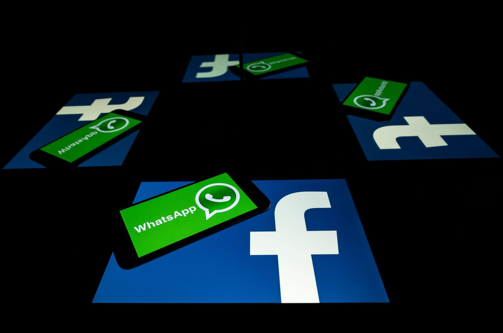 The logo of U.S. social network Facebook and mobile messaging service WhatsApp on the screens of a smartphone and a tablet in Toulouse, southwestern France, Oct. 5, 2020. (AFP Photo)