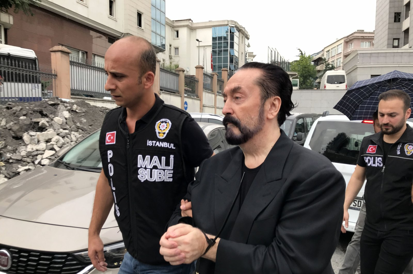Adnan Oktar is escorted by police after his arrest, in Istanbul, Turkey, July 11, 2018. (DHA PHOTO)