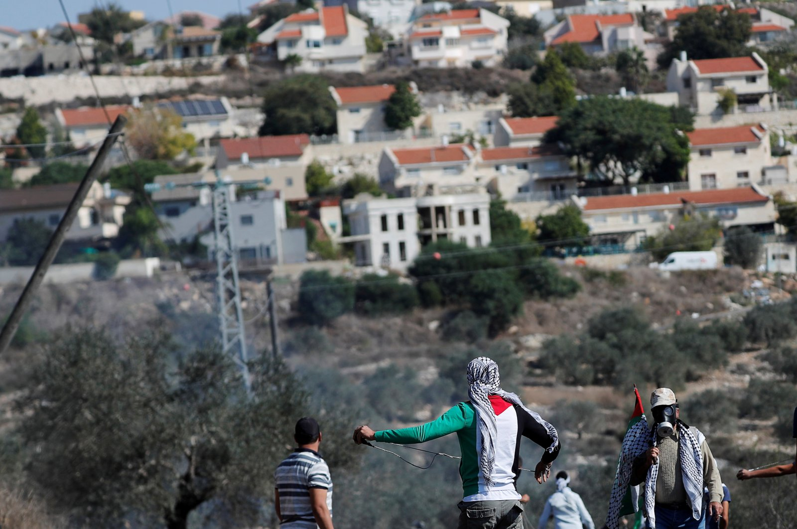 Palestinian demonstrators stand in front of a Jewish settlement during a protest, in Kafr Qaddum in the Israeli-occupied West Bank, Palestine, Nov. 13, 2020. (Reuters Photo)