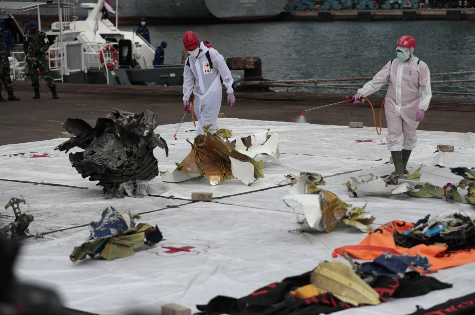 Workers spray disinfectant at parts of aircraft recovered from Java Sea where a Sriwijaya Air passenger jet crashed, at Tanjung Priok Port in Jakarta, Indonesia, Monday, Jan. 11, 2021. (AP Photo)