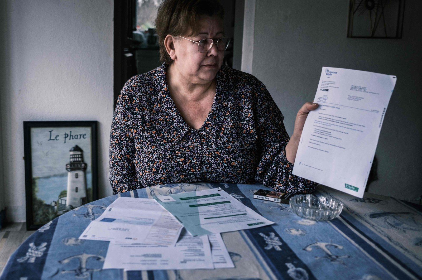 Jeanne Pouchain who, since November 2017, has been declared dead by the justice system after being convicted by the Prud'hommes, shows some paperwork, in Saint-Joseph, France, Jan. 8, 2021. (AFP Photo)