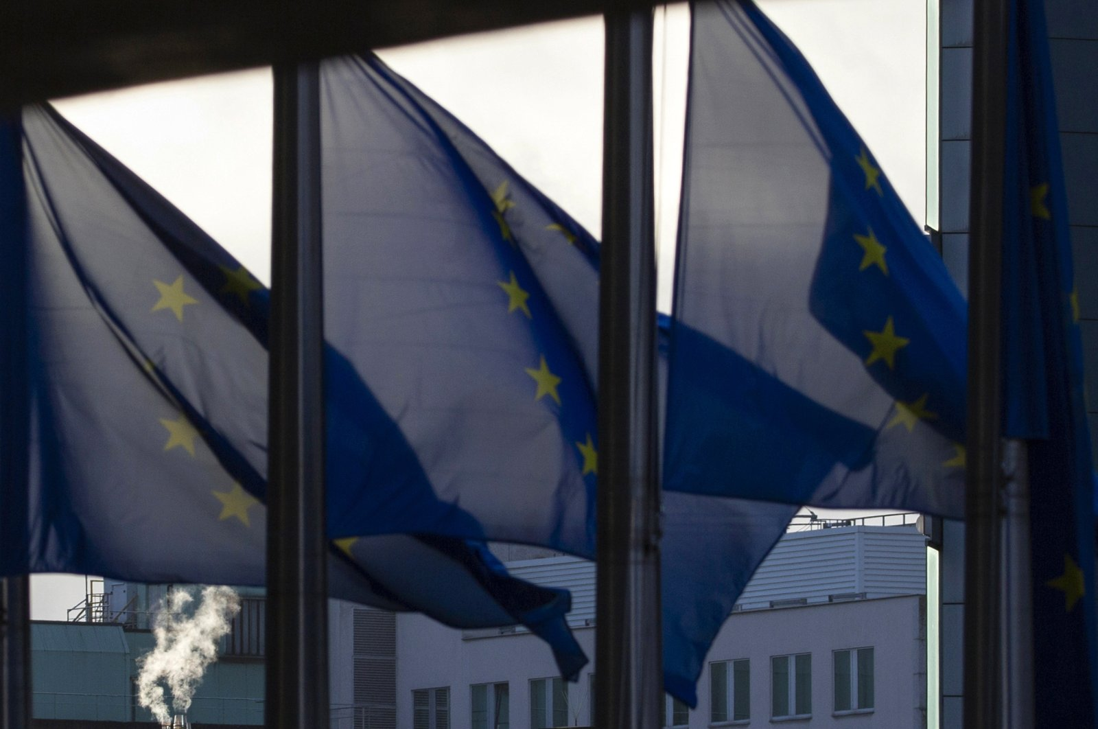 Smoke rises from a chimney behind EU flags fluttering in the wind outside EU headquarters in Brussels, Dec. 24, 2020. (AP Photo)