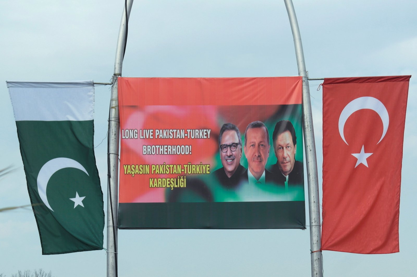 The national flags of Pakistan and Turkey are seen on poles next to a sign showing Pakistani President Arif Alvi (L), Turkish President Recep Tayyip Erdoğan (C) and Pakistani Prime Minister Imran Khan (R), in Islamabad, Pakistan, Feb. 13, 2020. (Reuters Photo)