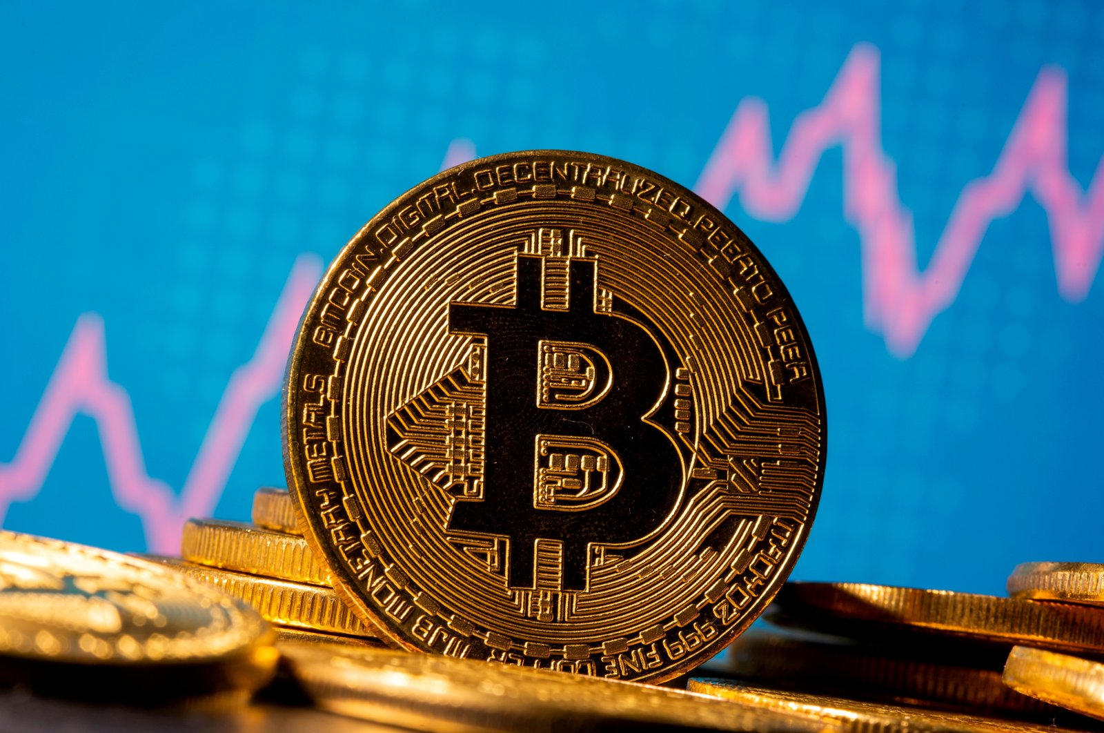 A representation of virtual currency Bitcoin is seen in front of a stock graph in this illustration taken November 19, 2020. (Reuters Photo)