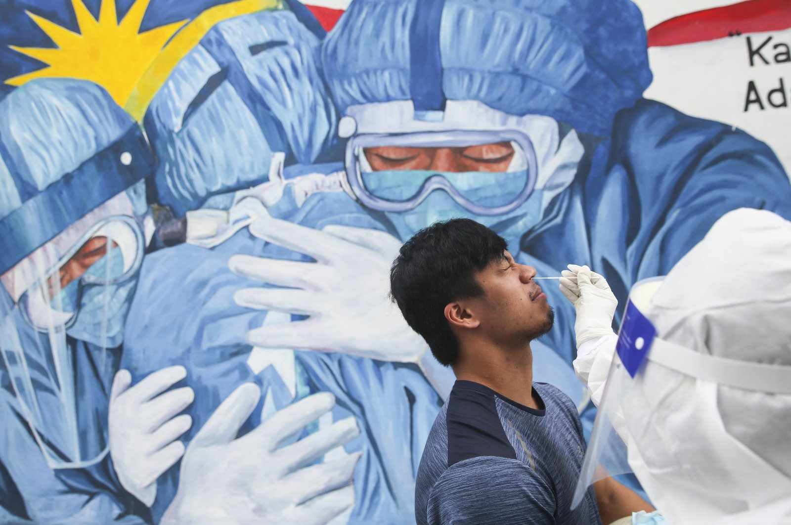 Medical personnel collects a swab sample from a man during a COVID-19 test at Ajwa clinic in Shah Alam, outside Kuala Lumpur, Malaysia, Jan. 11, 2021. (EPA-EFE Photo)