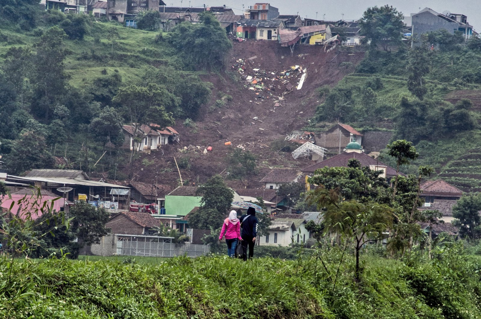 People walk past the site of a village that was hit by landslides on Sunday, in Sumedang, West Java, Indonesia, Jan. 11, 2021. (AP Photo)