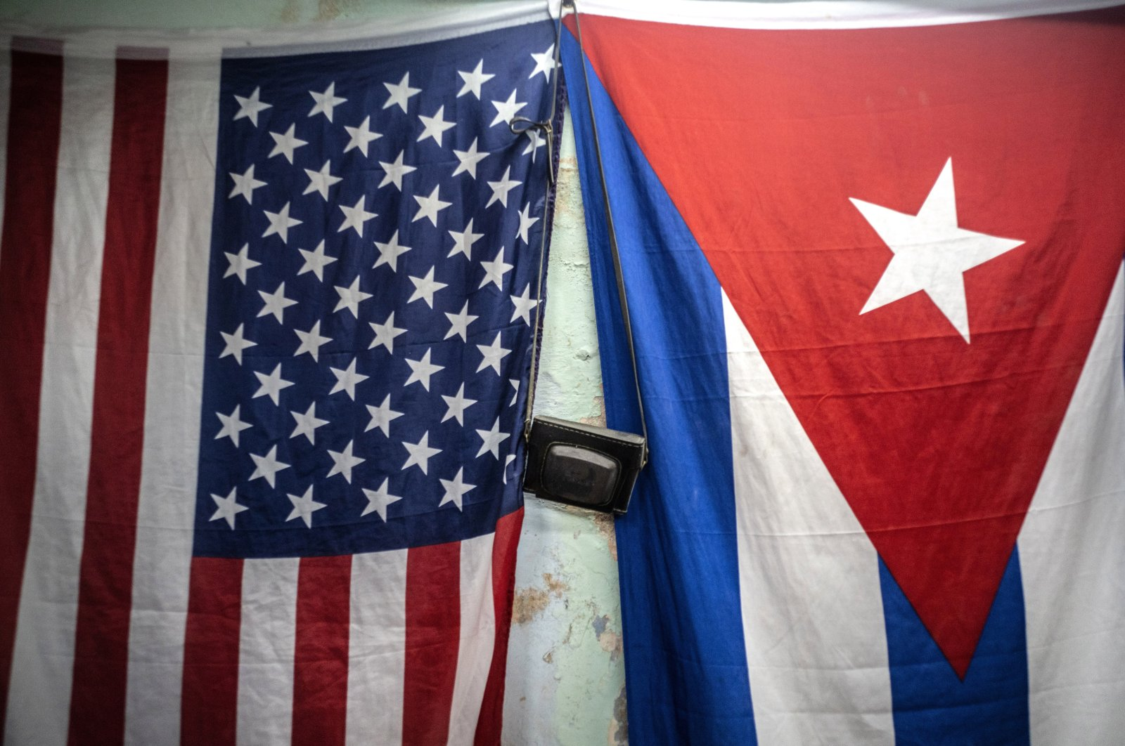 A U.S. and Cuban flags hang from a wall with an old photo camera hung in between in Havana, Cuba, Jan 11, 2021. (AP Photo)