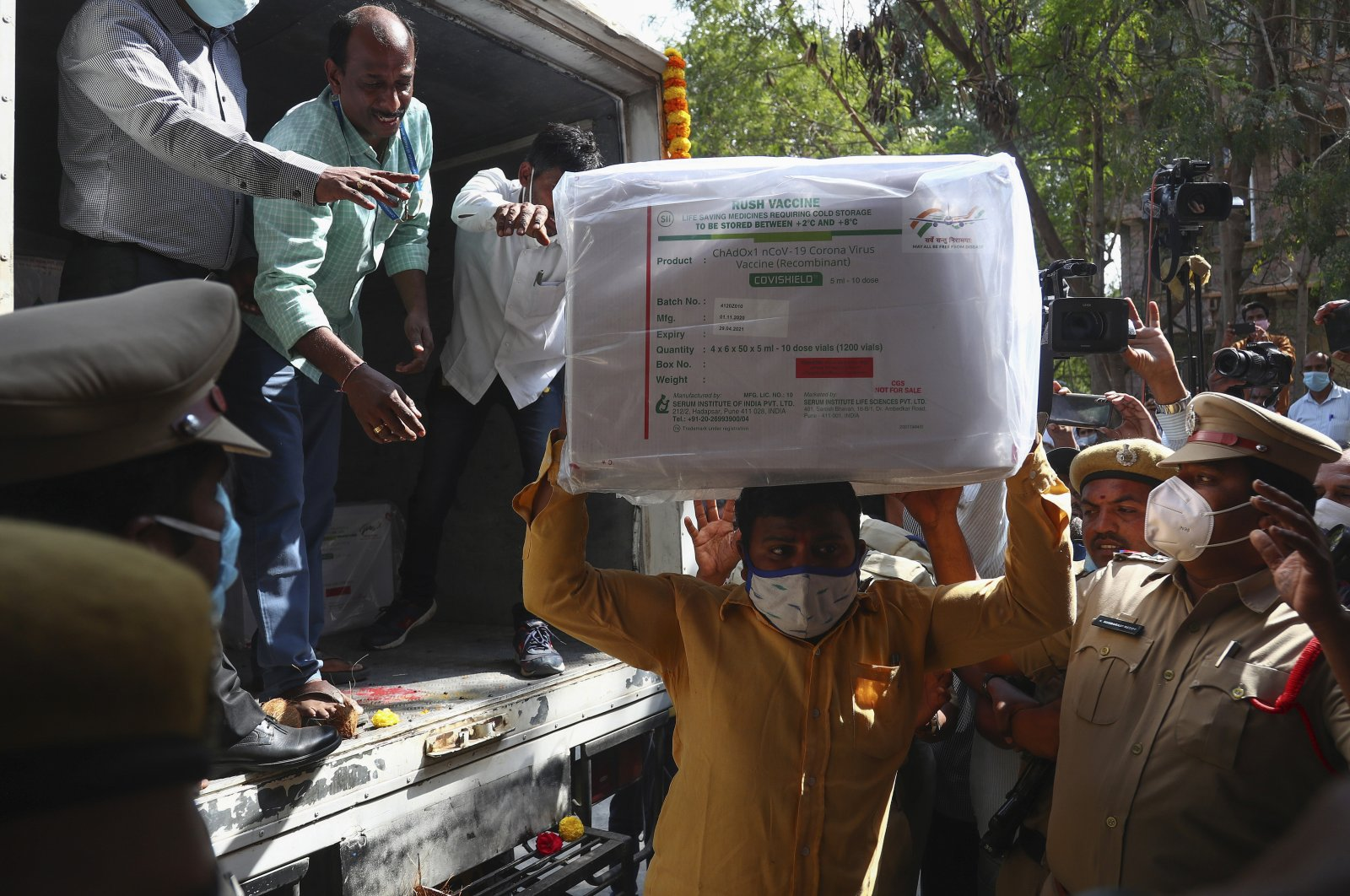 Health workers shift a box containing COVID-19 vaccines from a vehicle to a cold storage at Commissionerate of Health and Family Welfare in Hyderabad, India, Jan. 12, 2021. (AP Photo)
