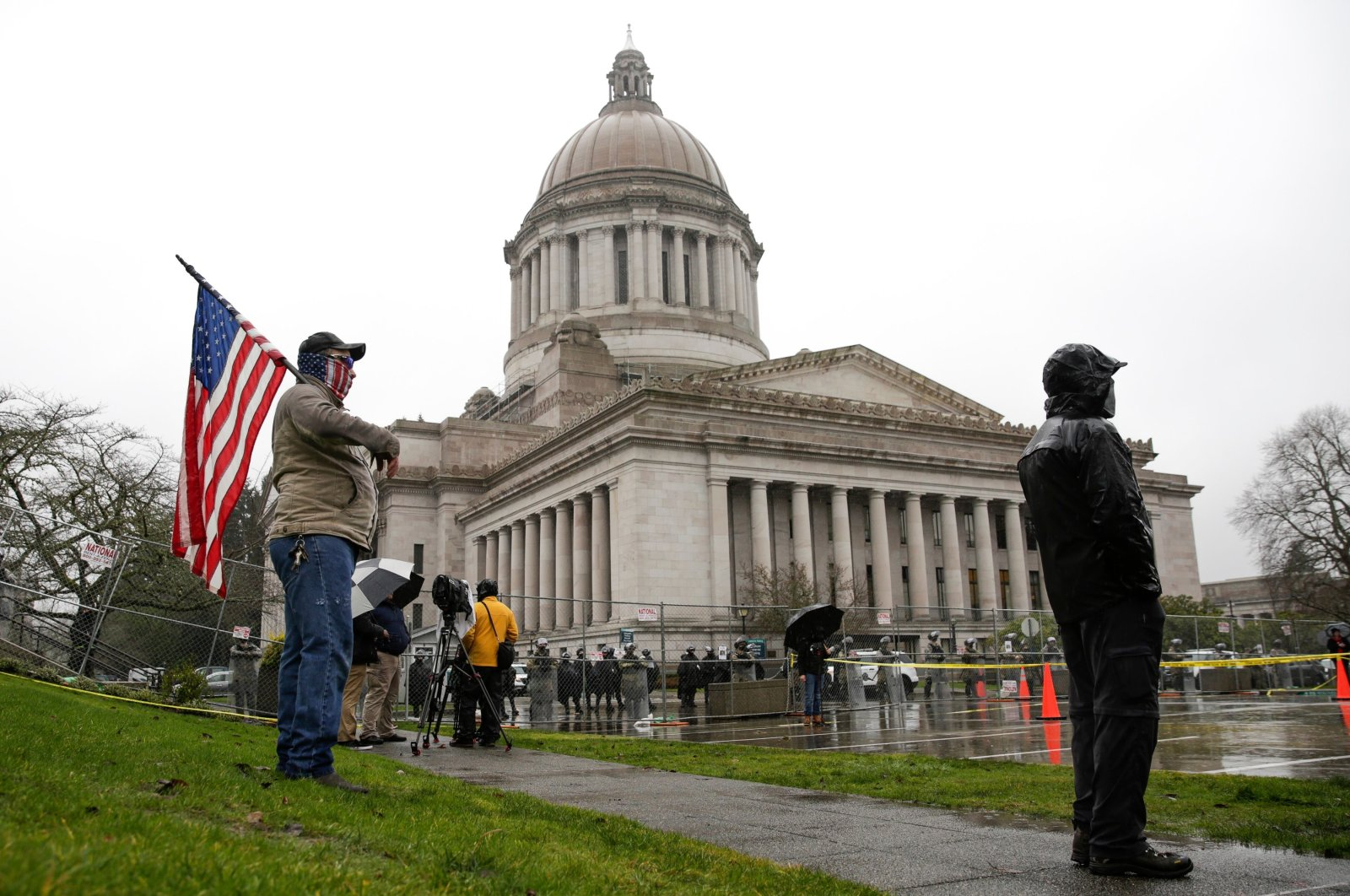 A demonstrator, who wished to remain anonymous, holds an American flag as the Washington National Guard, State Patrol and a fence surround the state Capitol as the Legislature opens the 2021 session in Olympia, Washington, Jan. 11, 2021. (AFP Photo)