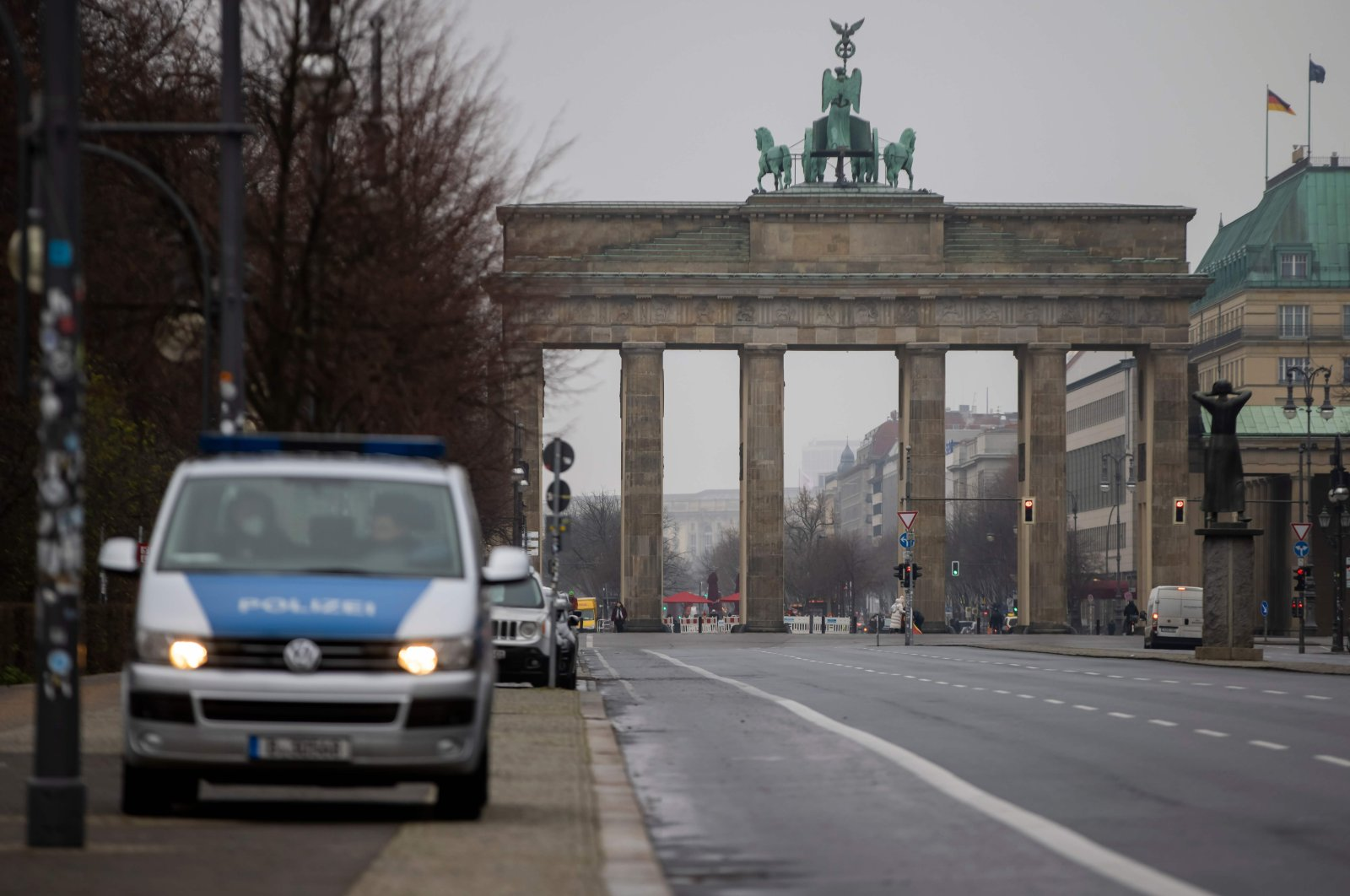 A police vehicle is seen at a virtually empty 17th of June street boulevard leading up to landmark Brandenburger Gate in Berlin, on Jan. 5, 2021. (AFP Photo)