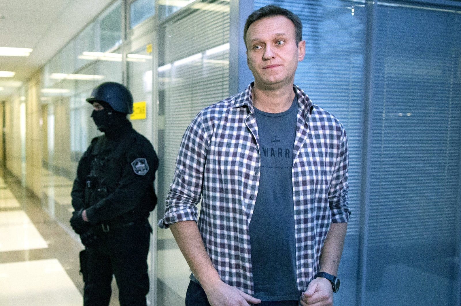 Russian opposition leader Alexei Navalny speaks to the media in front of a security officer standing guard at the Foundation for Fighting Corruption office in Moscow, Russia, Dec. 26, 2019. (AP Photo)