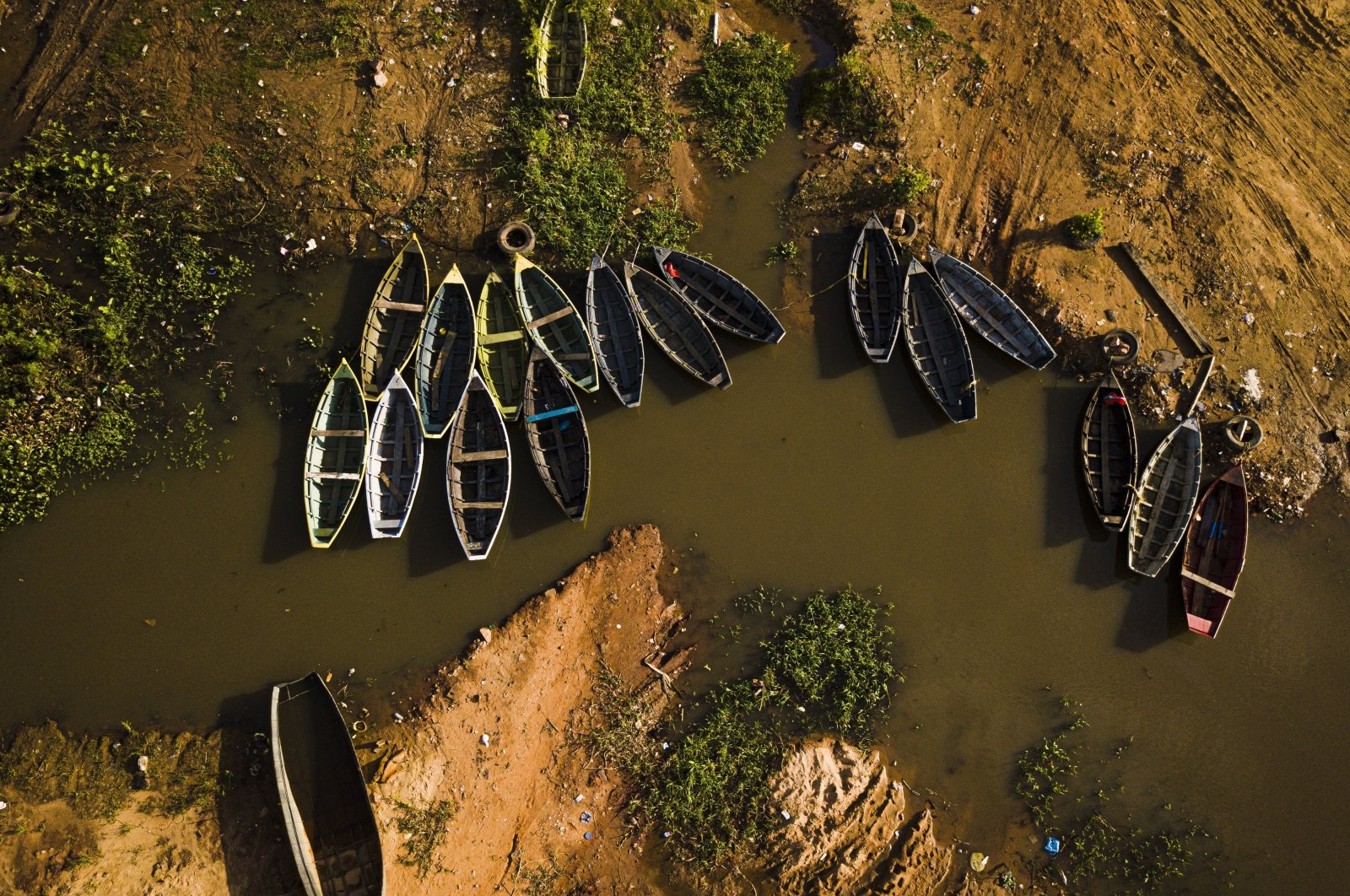 Fisherman's boats sit idle on the dry banks of a Paraguay River tributary in Puerto Pabla, Lambare, Paraguay, Jan. 12, 2021. (AP Photo)