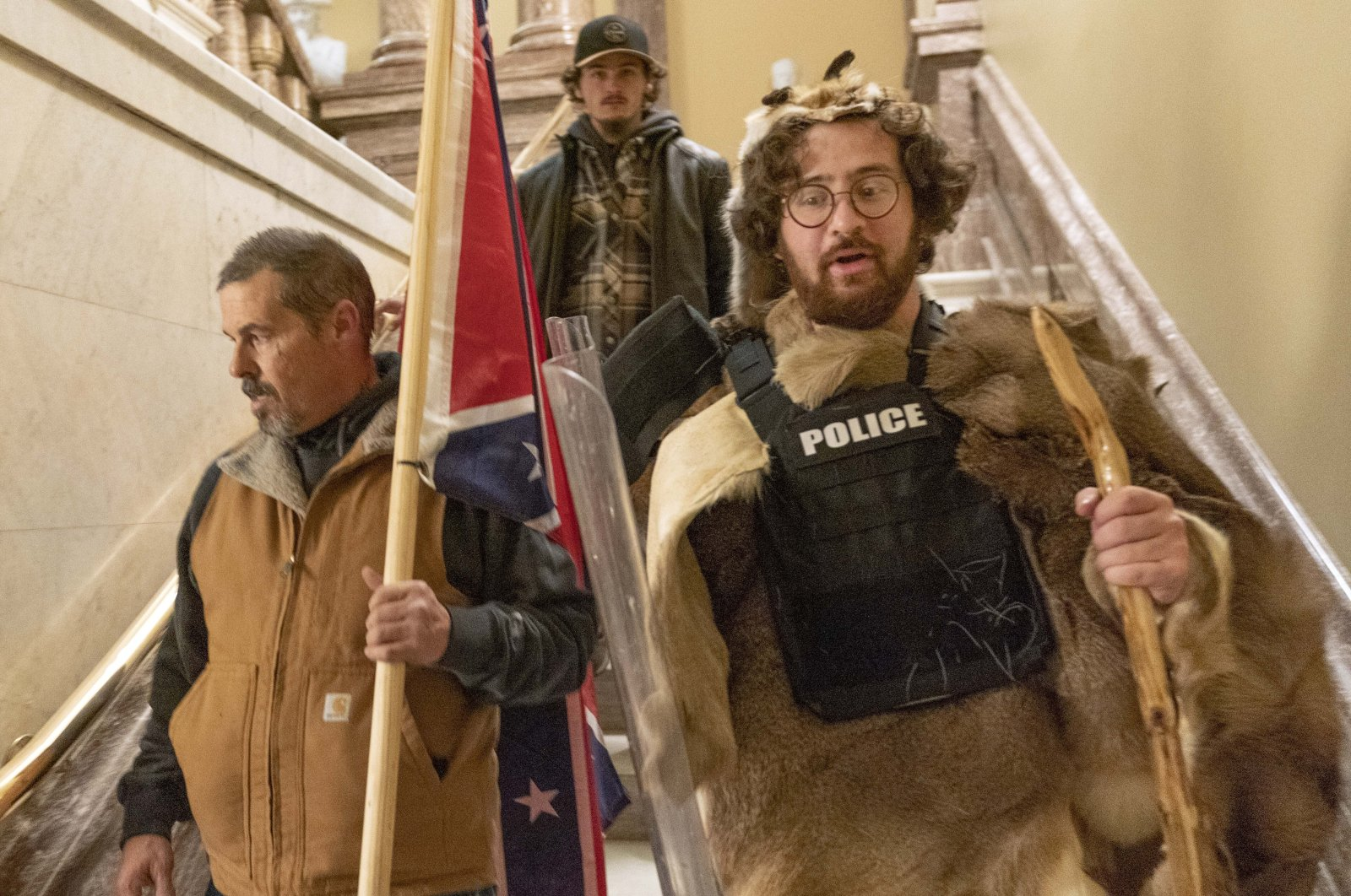 In this file photo, supporters of President Donald Trump, including Aaron Mostofsky (R), who is identified in his arrest warrant, walk down the stairs outside the Senate Chamber in the U.S. Capitol, in Washington D.C. on Jan. 6, 2021. (AP Photo)