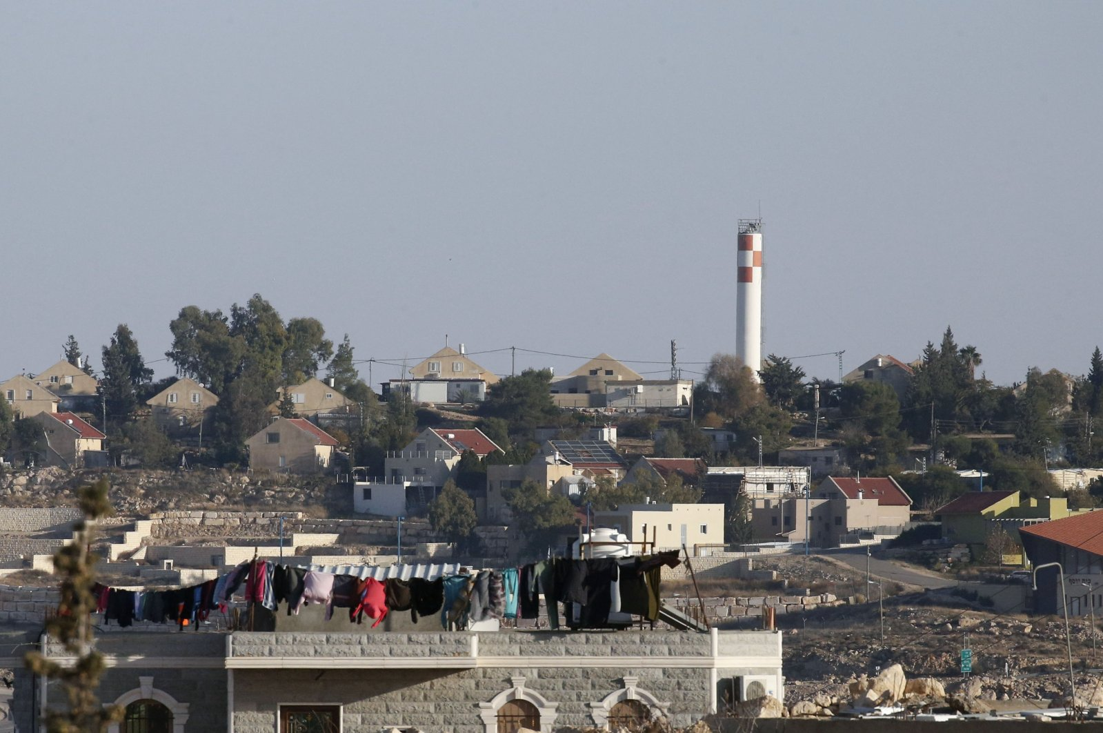 Clothes hang to dry on the roof of a house in the Palestinian village of al-Dirat near Yatta village, with a backdrop of the illegal Israeli settlement of Karmel in the southern area of Hebron city in the occupied West Bank, on Jan. 12, 2021. (AFP Photo)