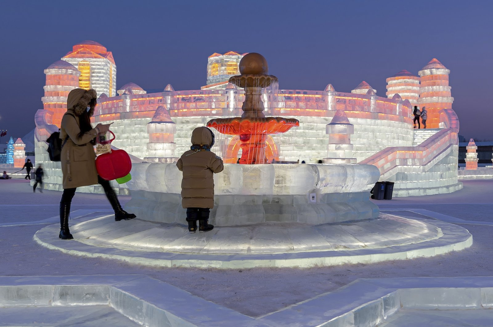 Visitors tour the annual Harbin Ice and Snow World in Harbin, Heilongjiang province, northeastern China, Jan. 5, 2021. (Chinatopix via AP)