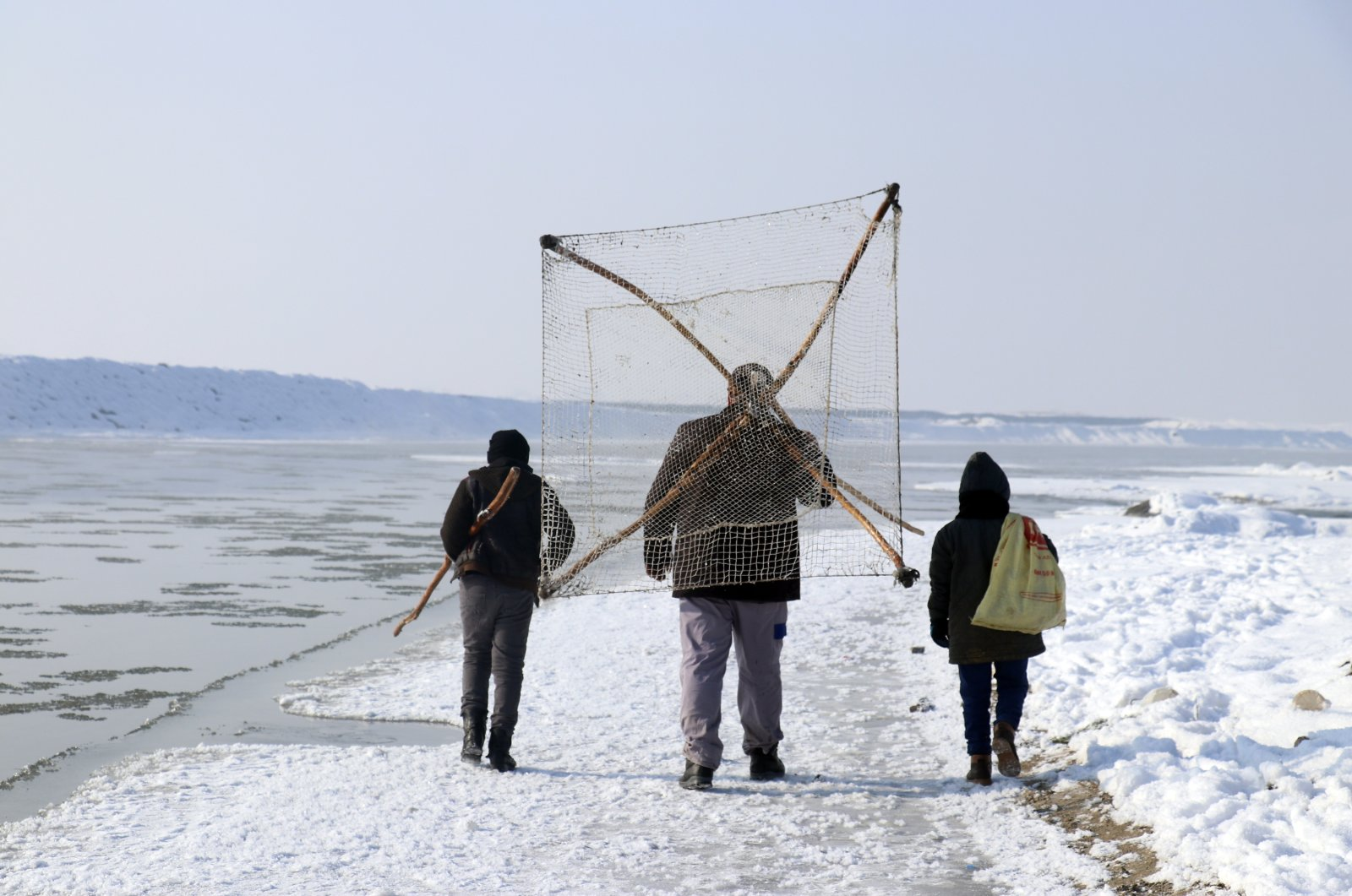 Fishermen carrying a net head out to catch what they can on the frozen Murat River in Ağri province, eastern Turkey, Jan. 12, 2021. (AA Photo)