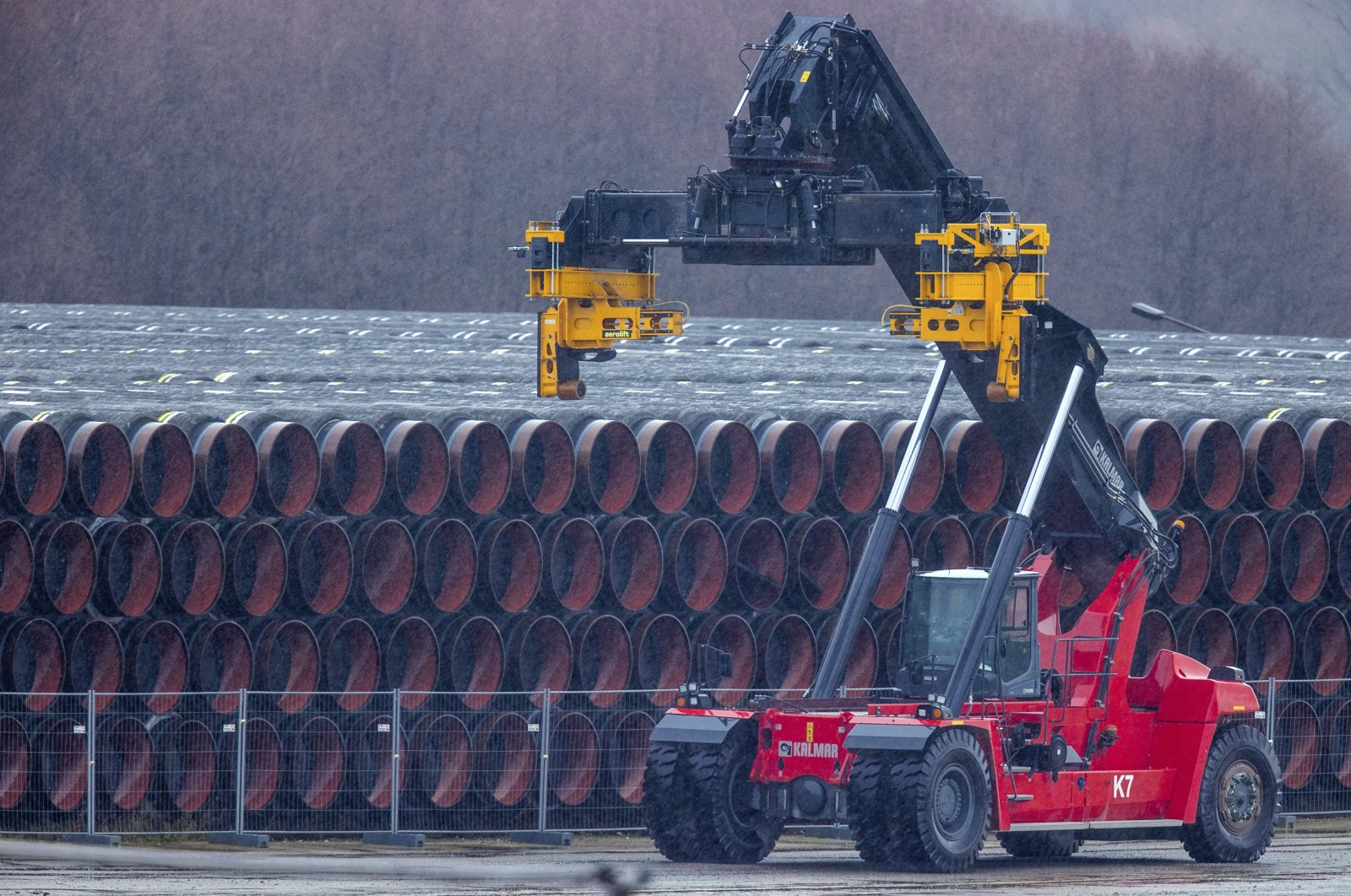 A special vehicle used to transport pipes for the Nord Stream 2 natural gas pipeline stands next to pipes at a storage yard in the port of Mukran in Sassnitz on the island of Ruegen, Germany on Jan. 6, 2021. (AP Photo)